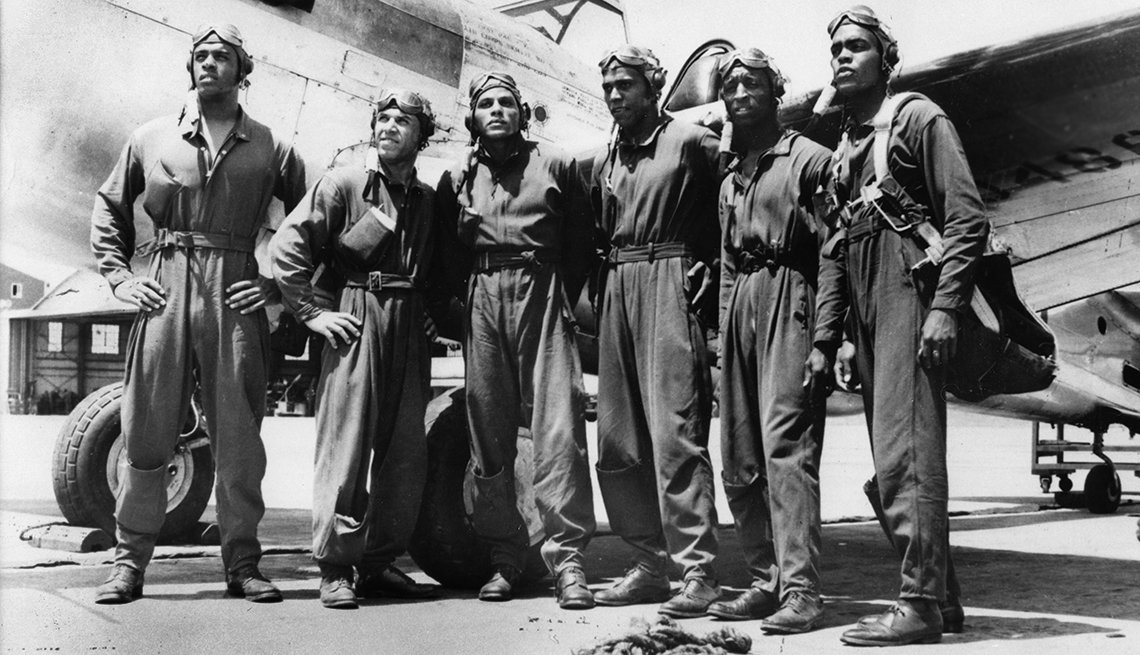 George Iles, third from left, with fellow Tuskegee Airmen and a Curtiss P-40 Warhawk.
