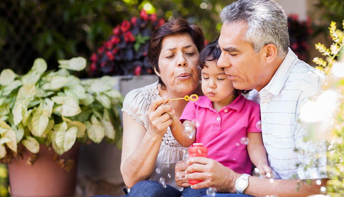 Dos abuelos soplan burbujas con un niño pequeño