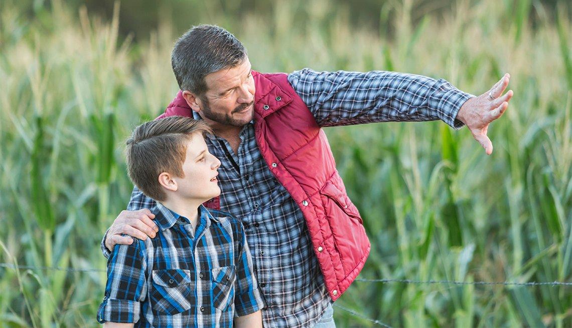 Un agricultor con su hijo, de 13 años de edad, de pie en un campo de cultivos.