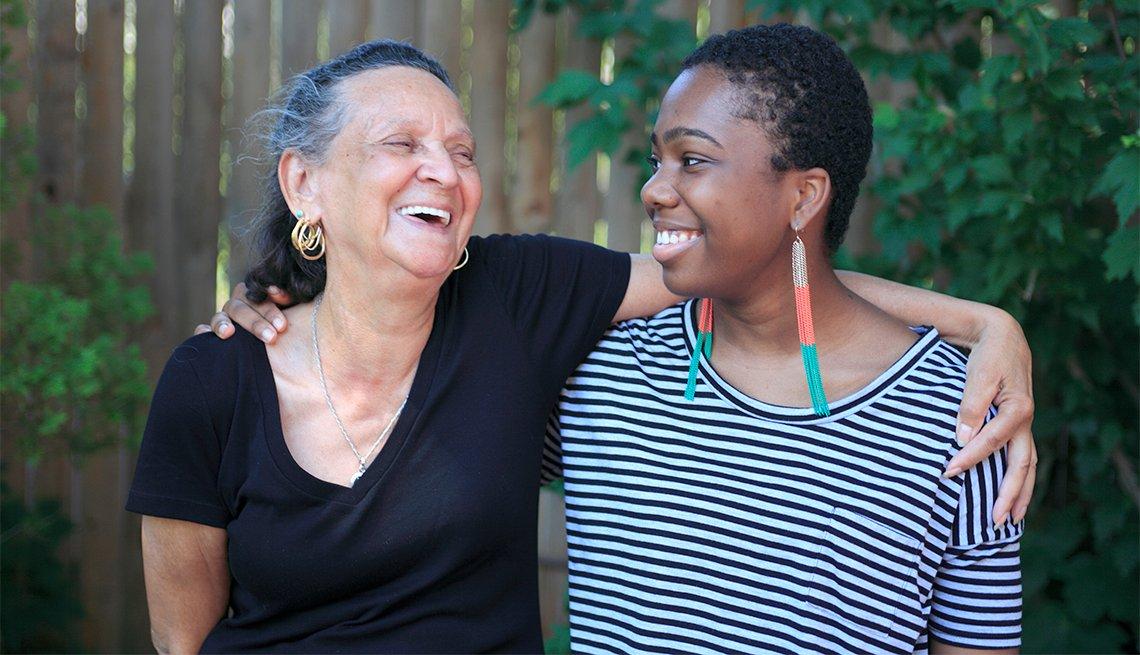 Abuela con nieta adolescente sonríen abrazadas.