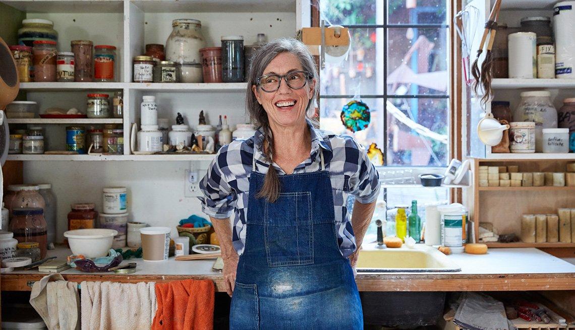 Retrato de mujer mayor con pelo gris dentro de su estudio de cerámica.
