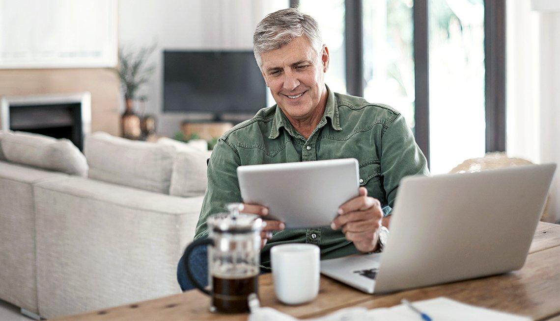 Hombre mayor usando una tableta electrónica y un computador en la mesa de su casa