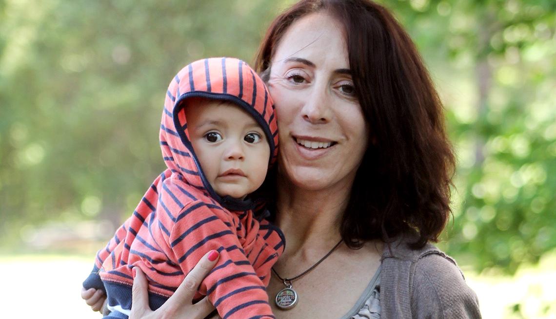 Mujer adulta sostiene a su bebé adoptado.