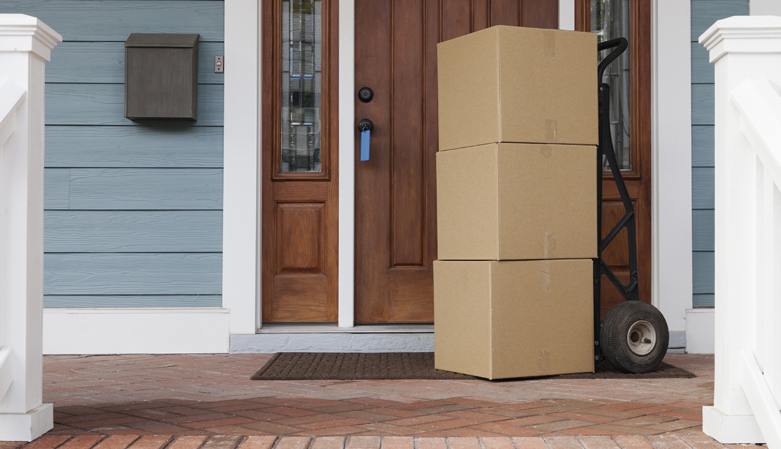 Moving boxes sitting on the front porch of a home.