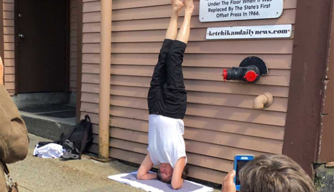 People gathered around taking photos of a woman doing a headstand.