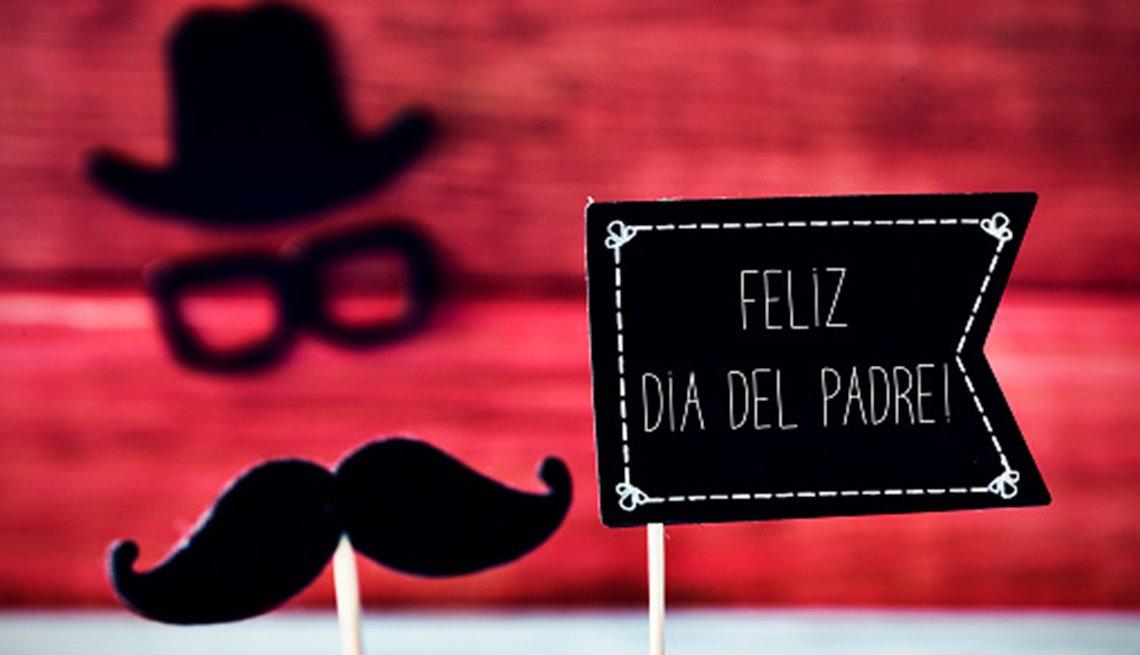 """Texto sobre una banderilla que dice""""Feliz día del padre"""" y un bigote, un par de anteojos y un sombrero que forma la cara de un hombre."""