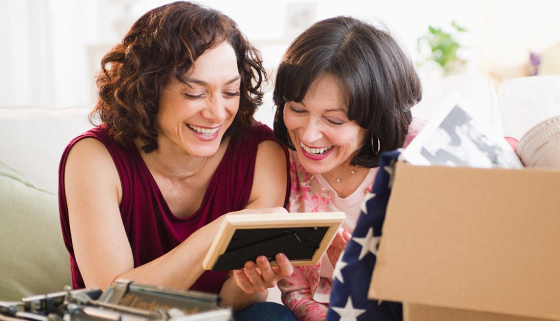 Dos mujeres mayores observan un portaretrato y sonríen.