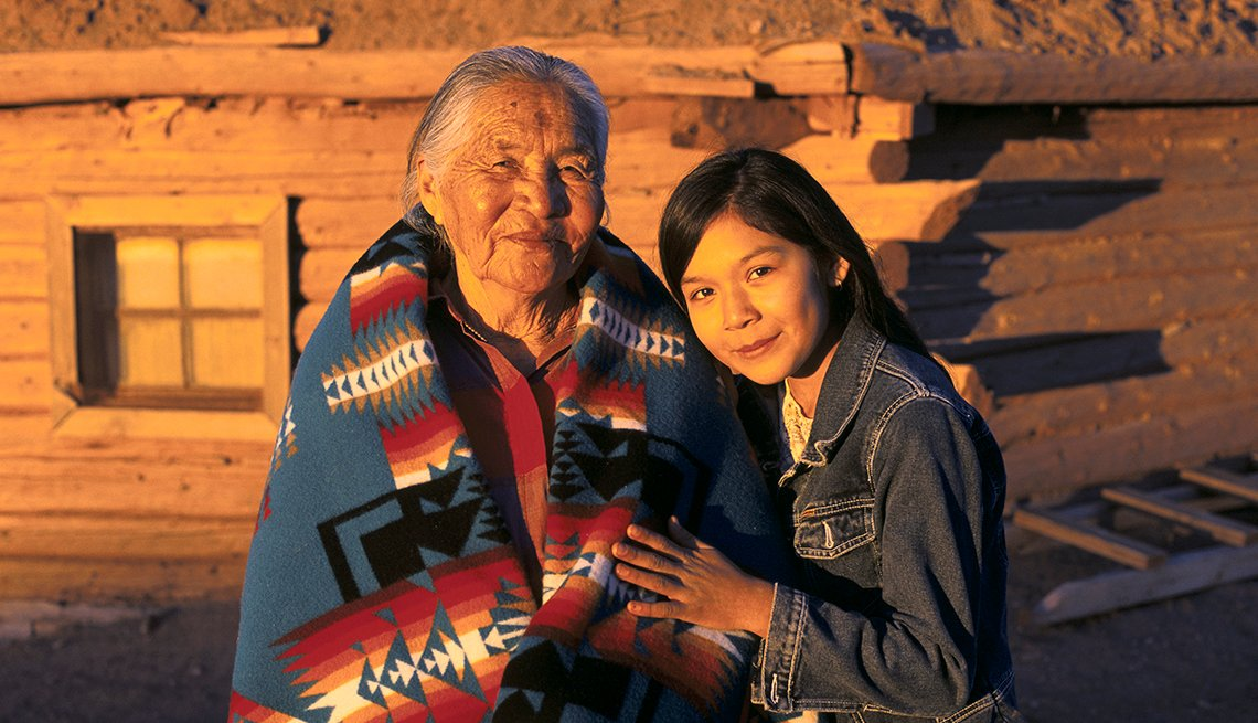 A Native American elder and younger Native American woman standing in front of their hogan in Arizona.