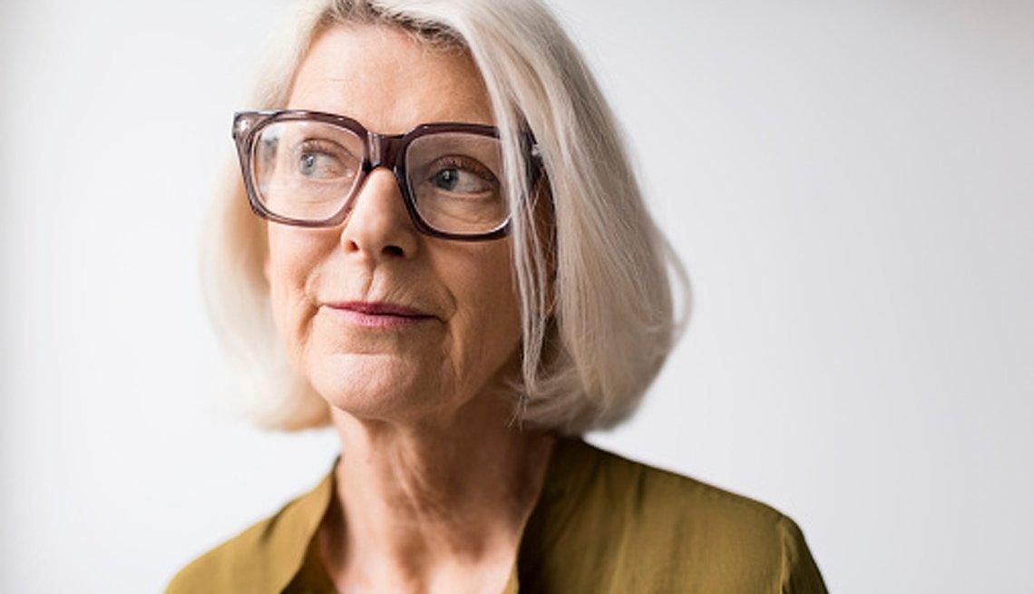 Mujer mayor con gafas y con cara de pensativa.