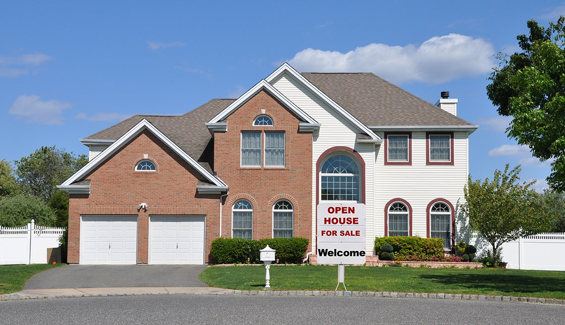 Large home with for sale sign in yard