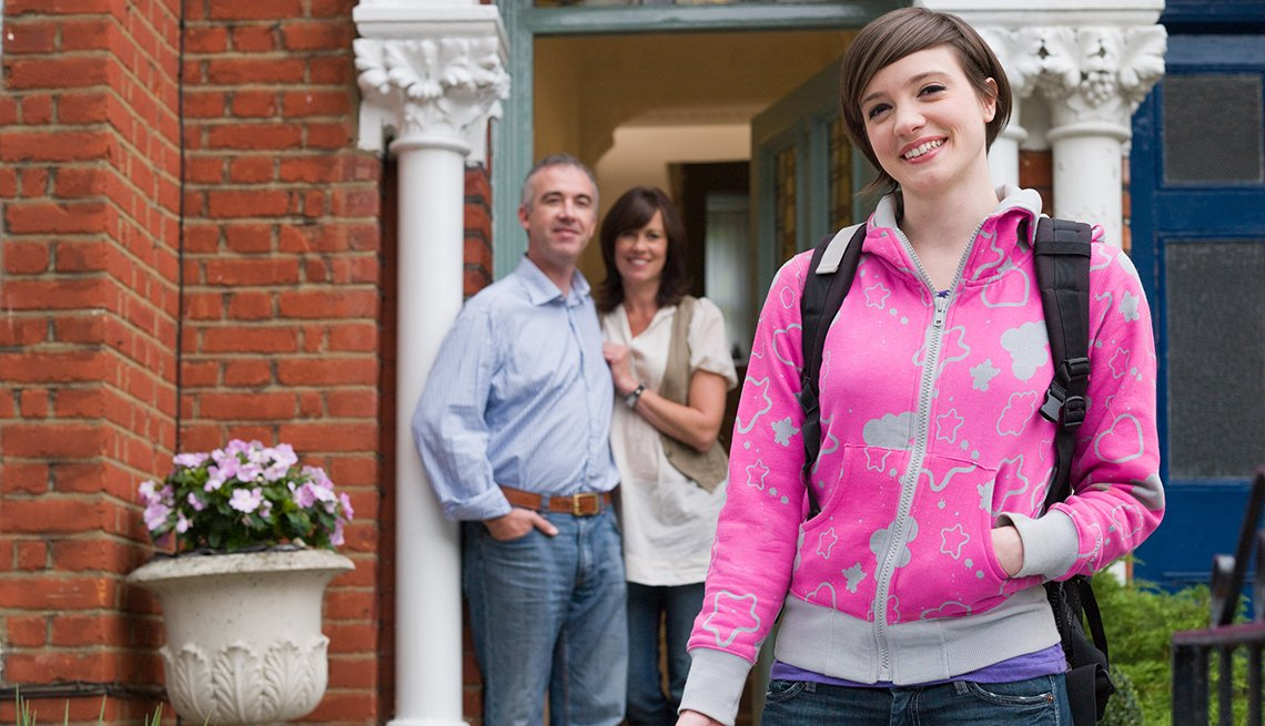 Los padres de una mujer joven ven a su hija mientras sale de su casa caminando.