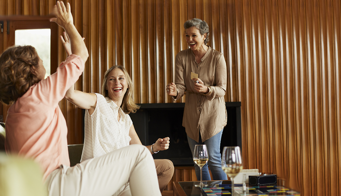 Cheerful friends enjoying indoor games at home