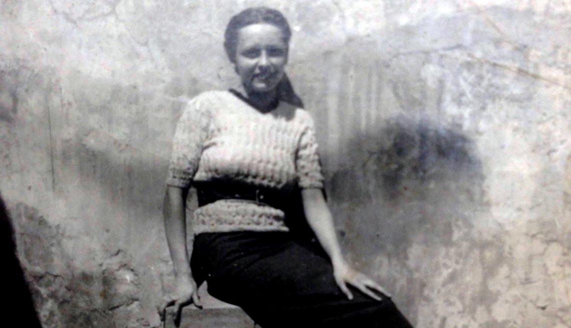 Foto antigua de una mujer que sonríe mientras está sentada.