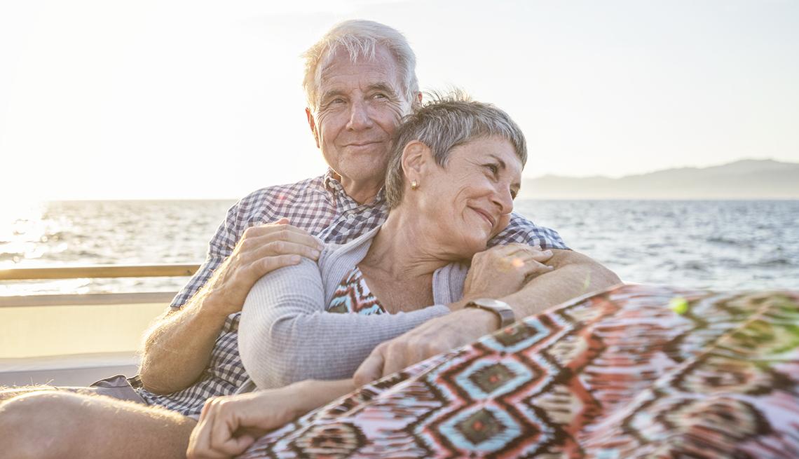 Una pareja de adultos mayores se abraza mientras están sentados en la playa.