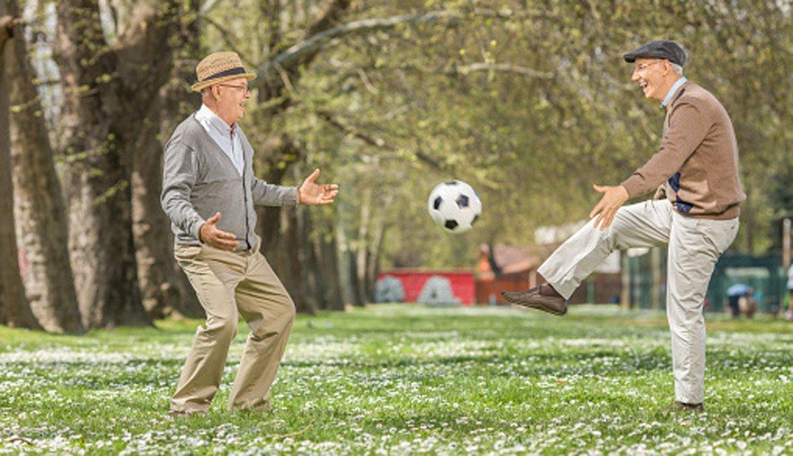 Dos hombres mayores juegan con un balón de fútbol.