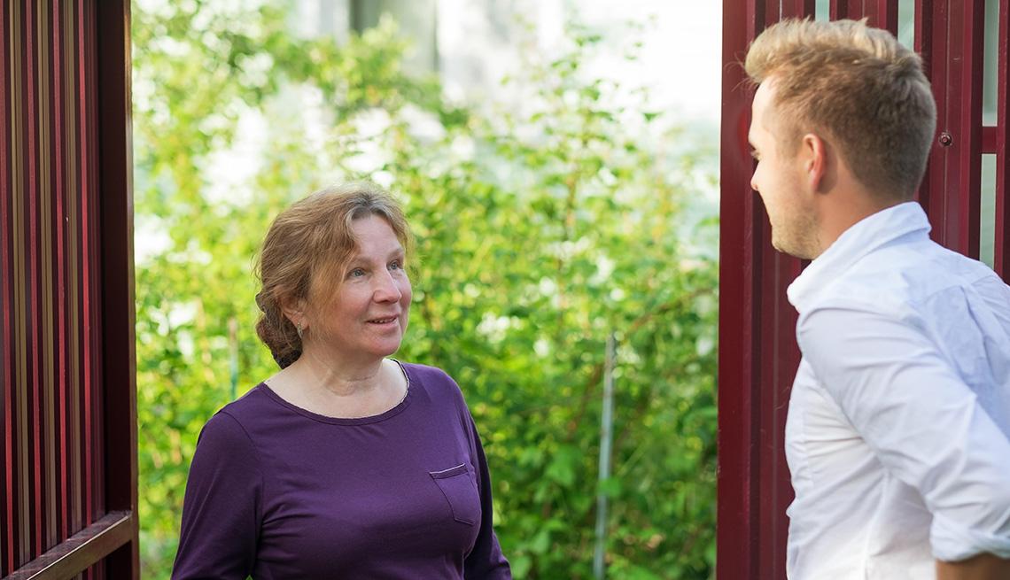 Mujer mayor abre la puerta de su casa a un hombre mientras sonríe.