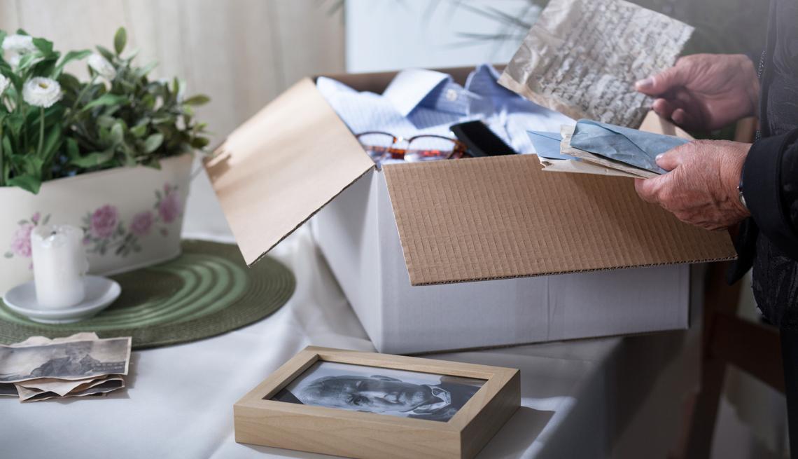 Un hombre mayor pone objetos familiares dentro de una caja.