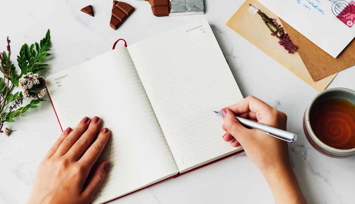 Una persona se prepara para escribir en un cuaderno.