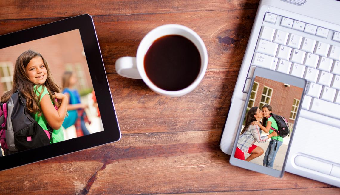 Tableta electrónica y teléfono muestran fotos. Al lado tienen una taza de café y una computadora portátil.