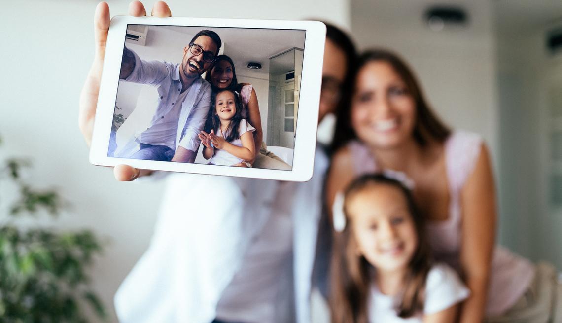 Una pareja y su hija se toman una foto con el teléfono inteligente.