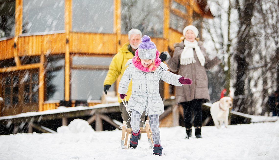 grandparents watching grandchild play in the snow