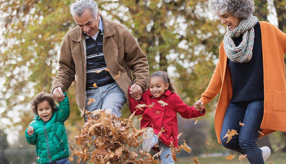 Grandparents and grandchildren walking through leaves