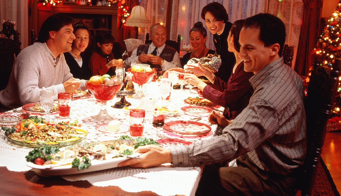 A family sitting around a dinner table having a holiday meal.