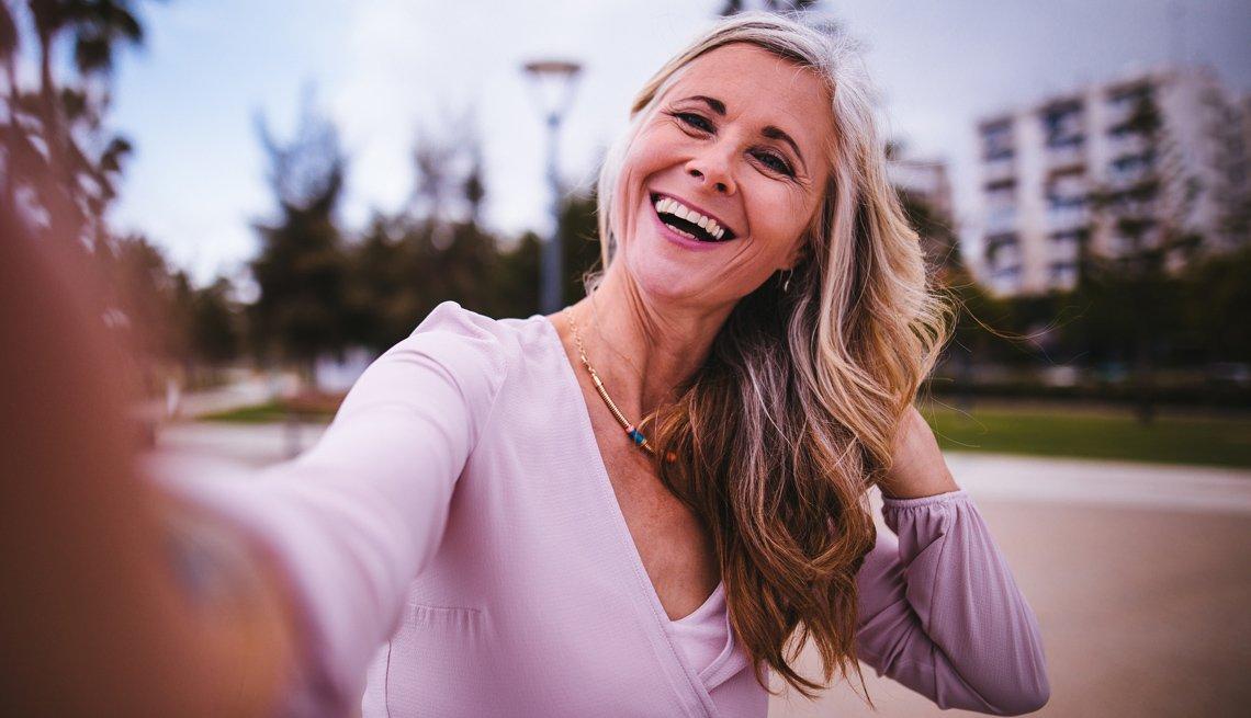 Mujer mayor se toma fotos a sí misma mientras sonríe.