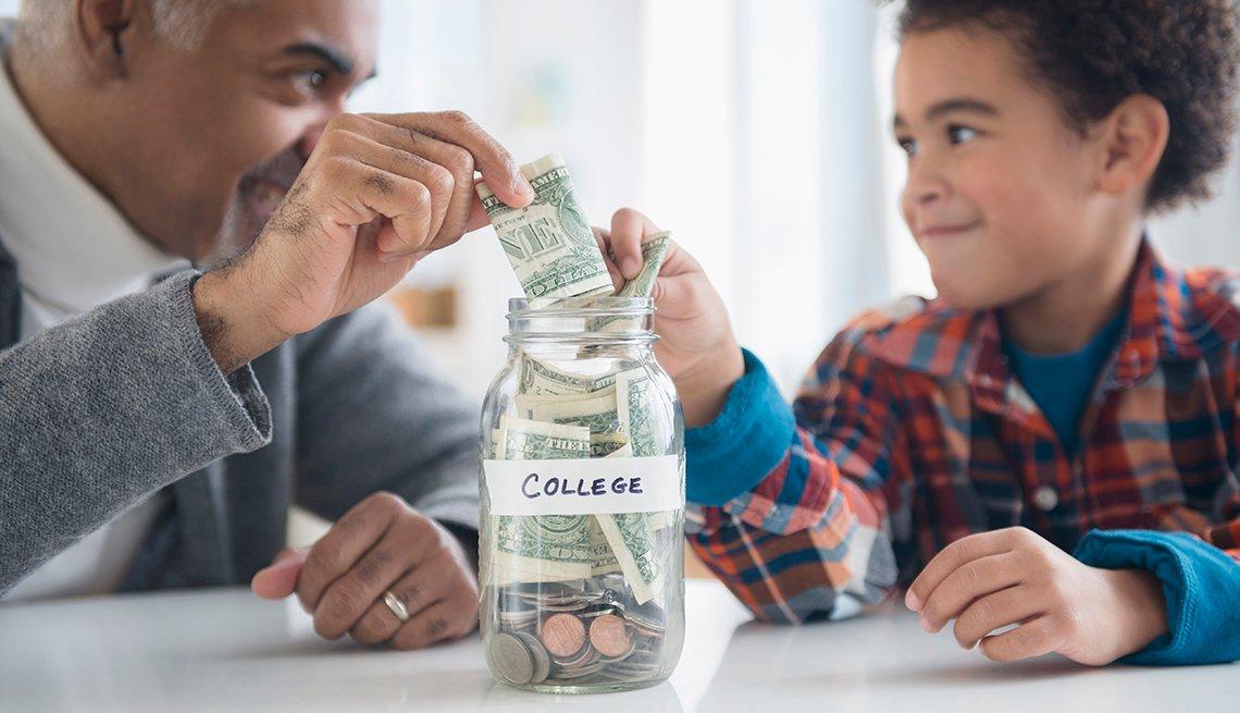 Un hombre mayor y un niño poniendo dinero en un frasco