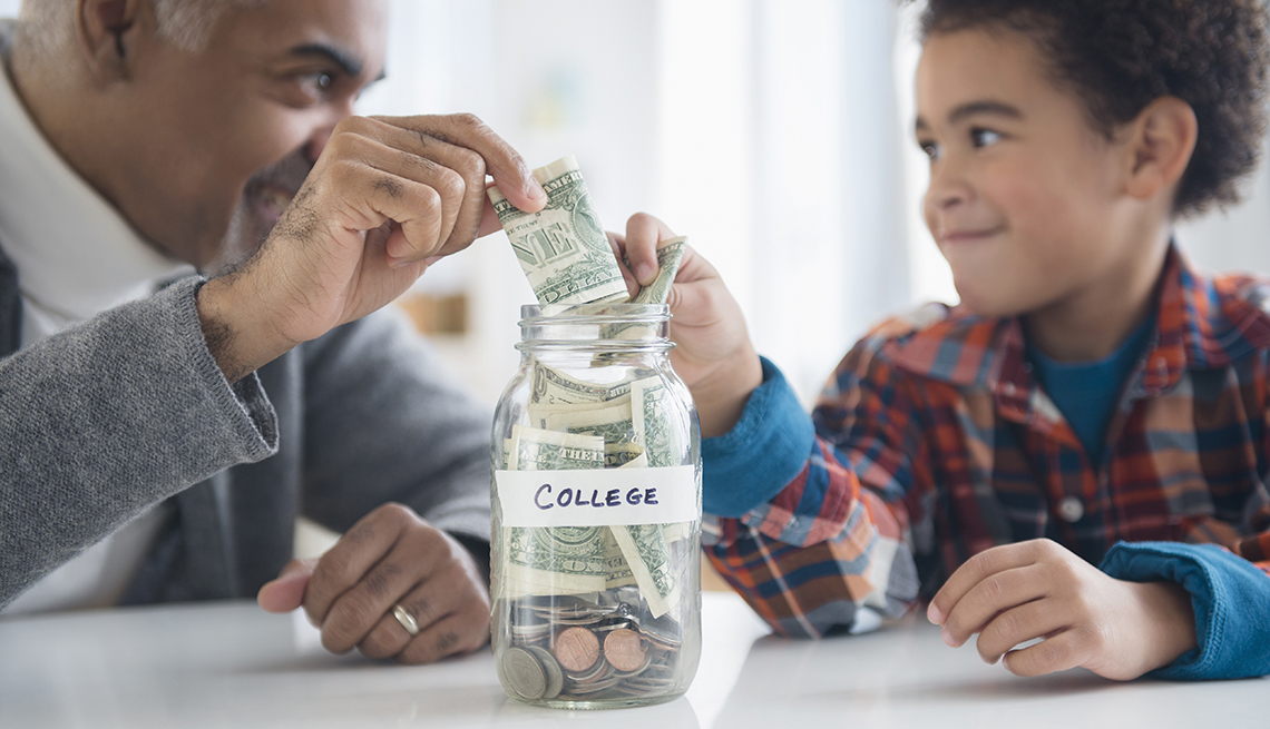 "an older man and child putting money in a jar labeled ""college"""