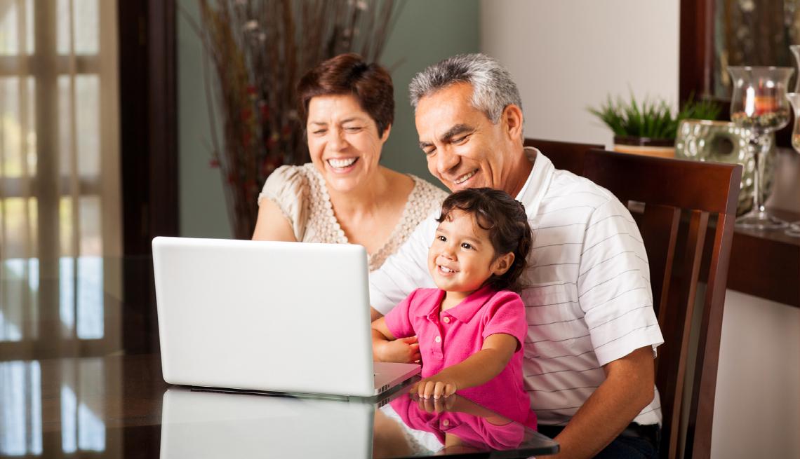 Abuelos sonríen con su nieta mientras ven la pantalla de una computadora