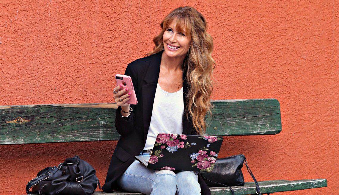 Lorraine Ladish sostiene en la mano un teléfono móvil