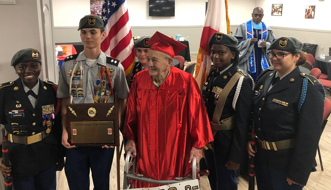 item 6, Gallery image. Joe Perricone receives a plaque from the Junior ROTC battalion at Hillsborough High School before the graduation ceremony.