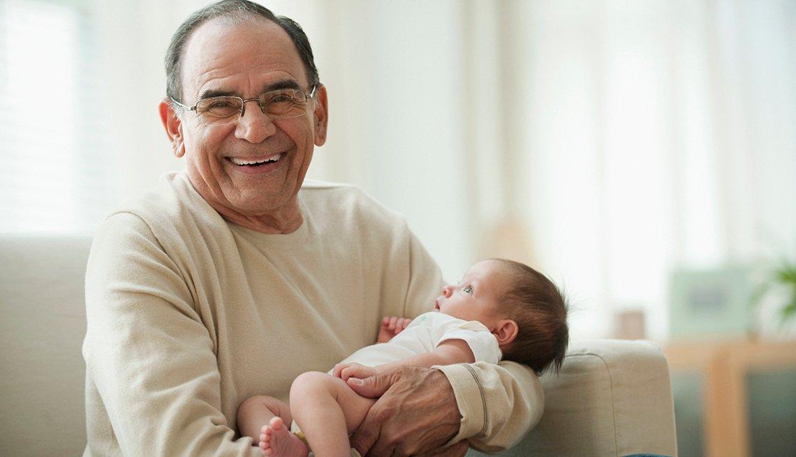 Abuelo sostiene a un bebé mientras está sentado, sonríe a la cámara
