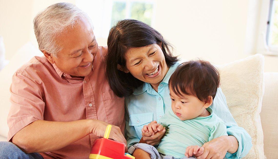Abuelos y su nieto en un sofá jugando con un juguete