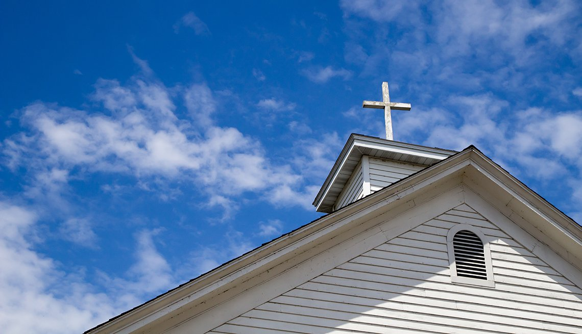 white church steeple with cross and blue sky