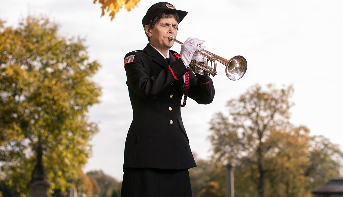 A woman plays a bugle at a military funeral