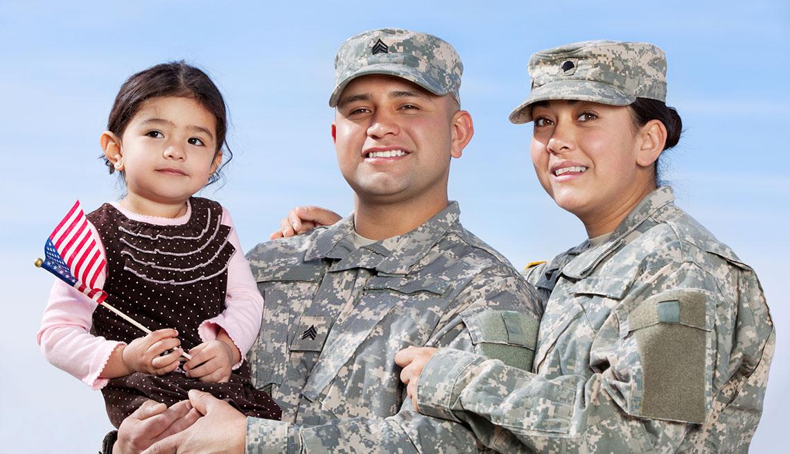 Pareja vestida con uniforme militar posa junto a su hija para una foto