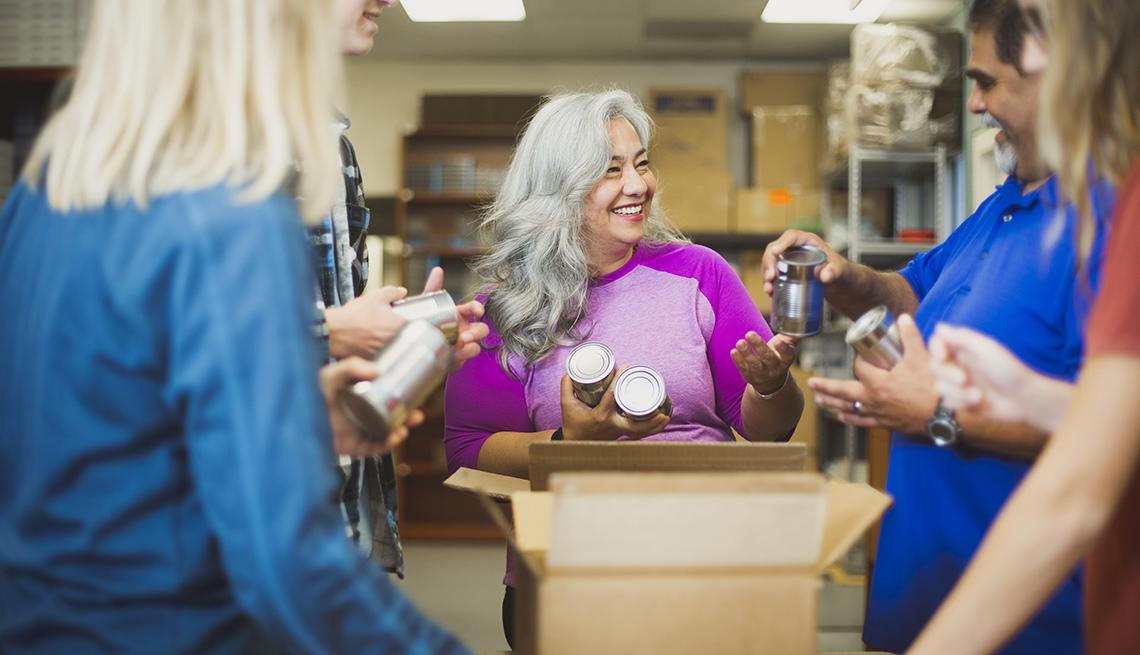 Hombres y mujeres se paran alrededor de una caja empacando productos enlatados