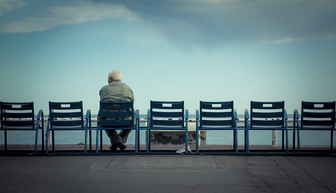 Hombre sentado en una línea de asientos vacios