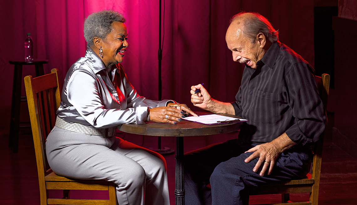 An older man and woman sitting at a table laughing