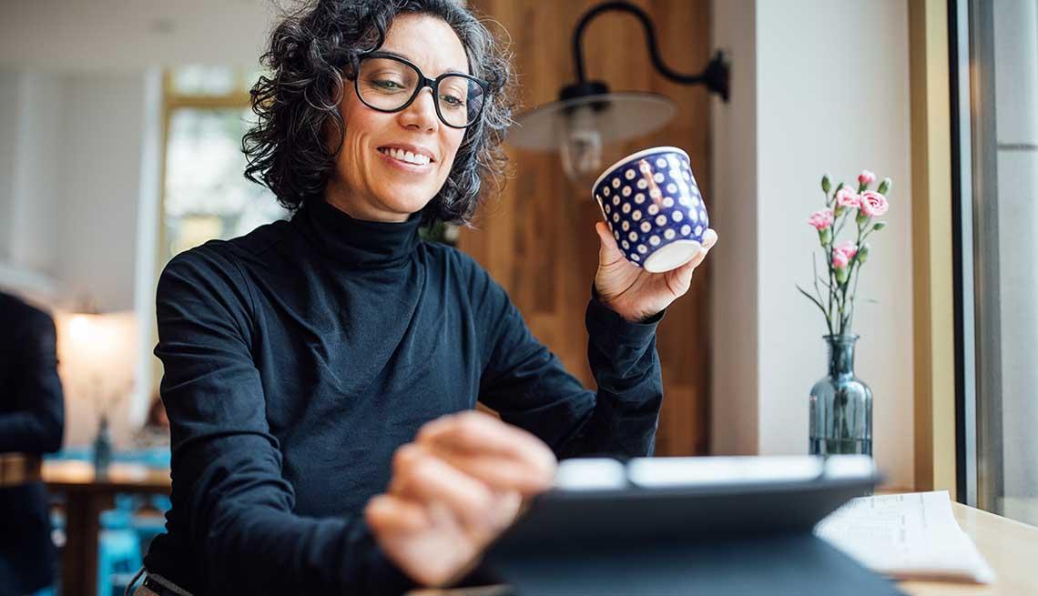 Mujer sonriendo mientras sostiene una tableta electrónica en una mano y una taza de café en la otra