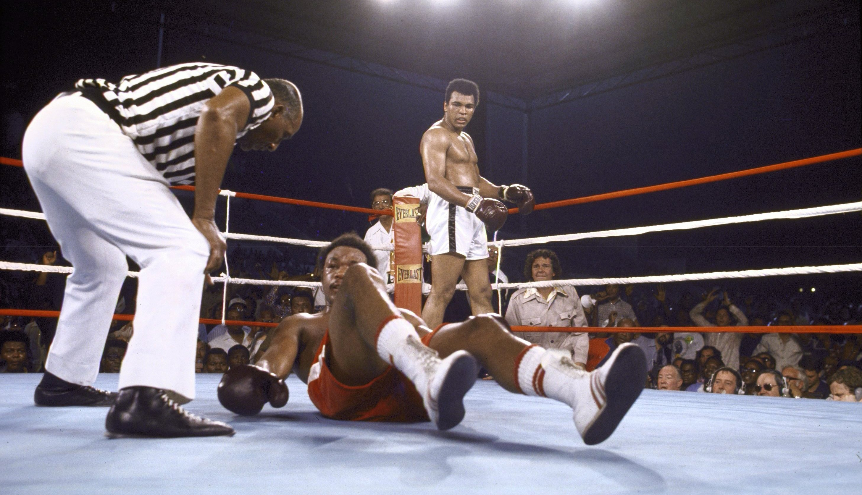 George Foreman tries to get off the canvas as referee Zack Clayton checks on him during the match against Muhammad Ali at 20th of May Stadium. Kinshasa, Zaire 10/30/1974