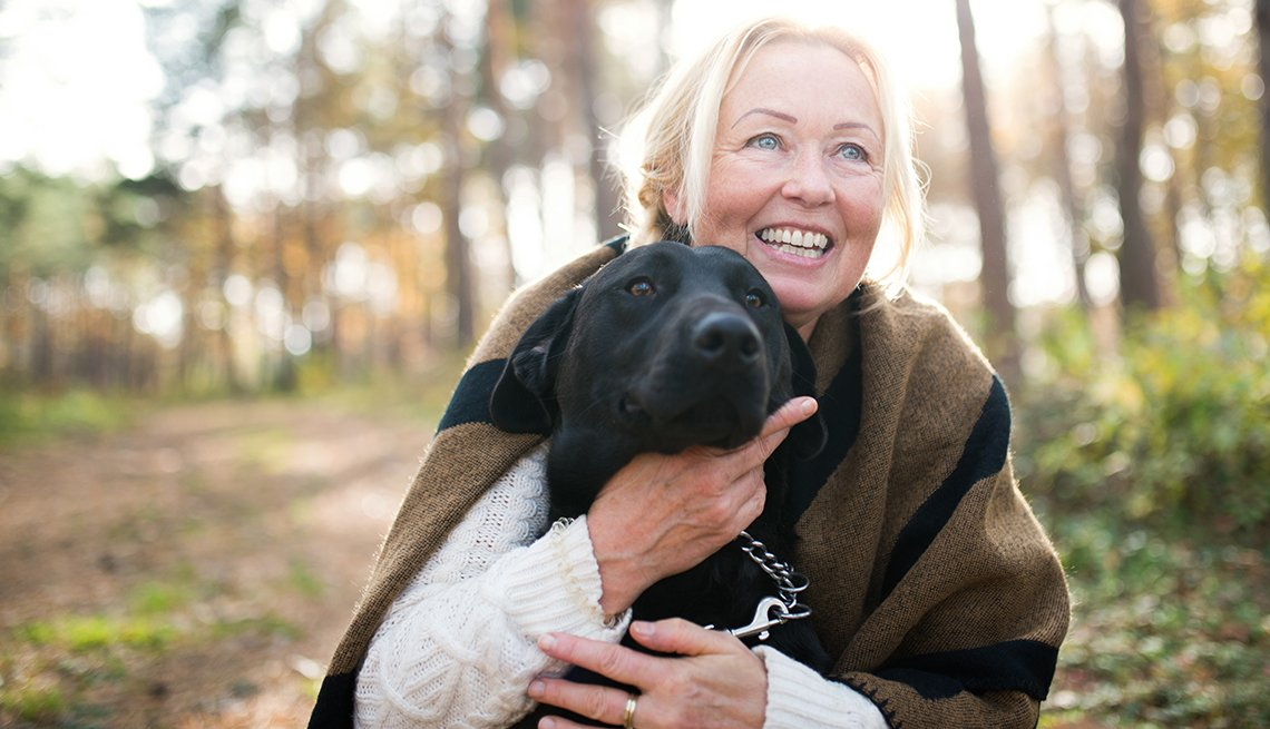 Mujer abraza a un perro de color negro