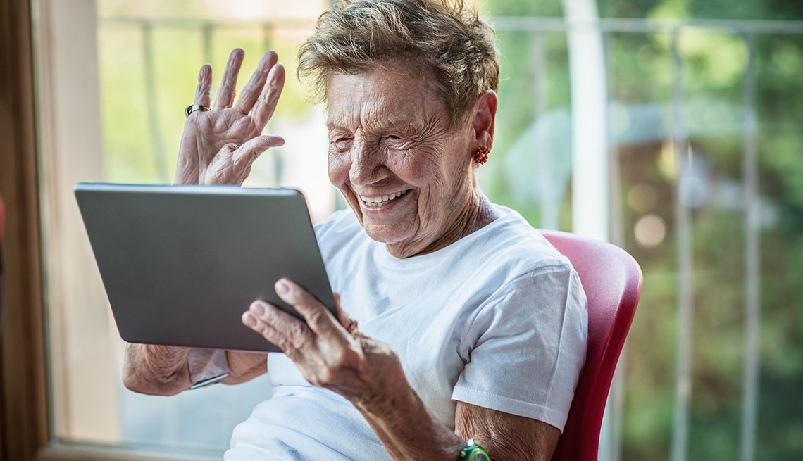 A mature woman using digital tablet on apartment balcony