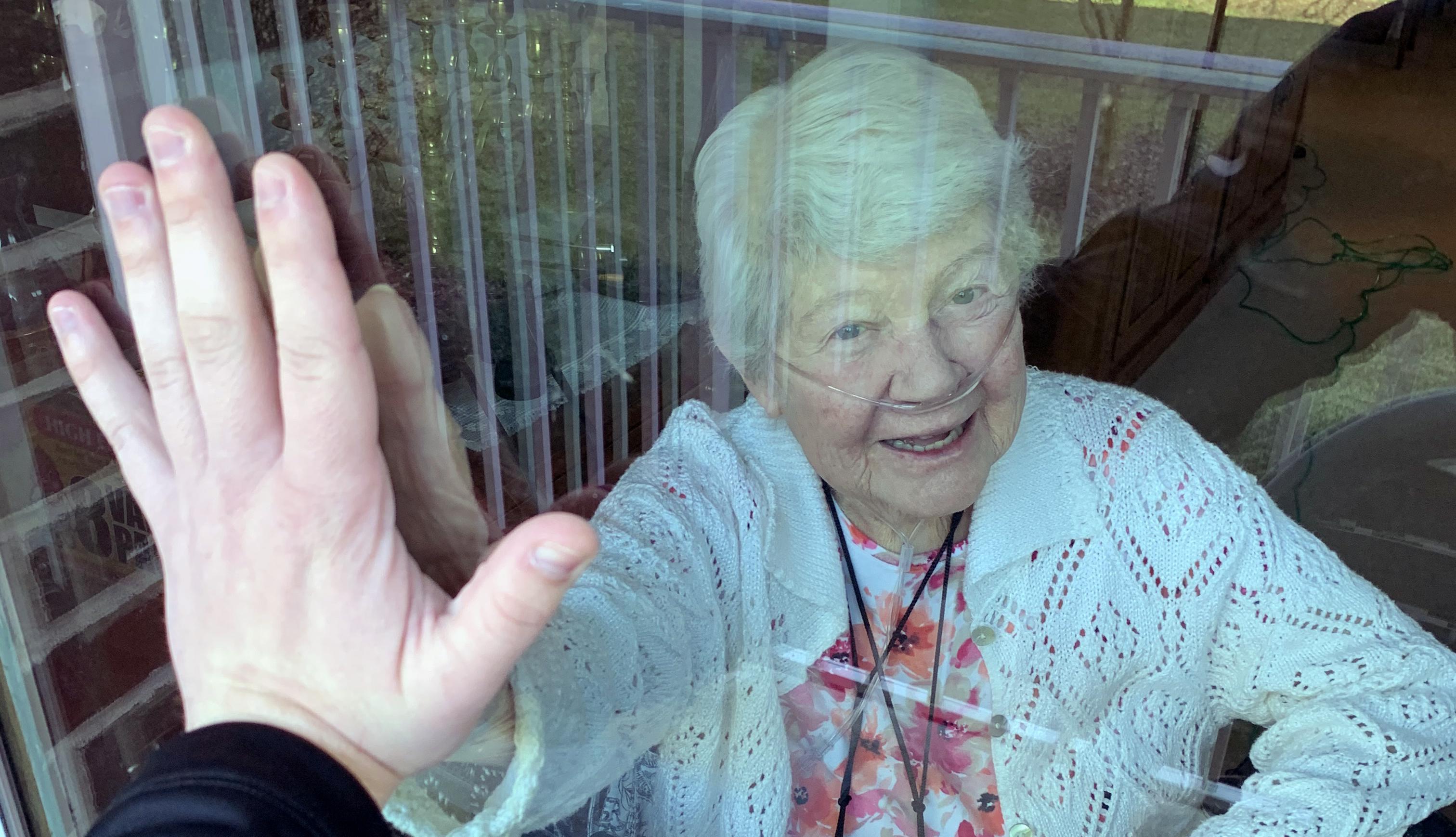 Un residente de un hogar de ancianos y una persona fuera de la ventana superponen las manos a ambos lados del cristal
