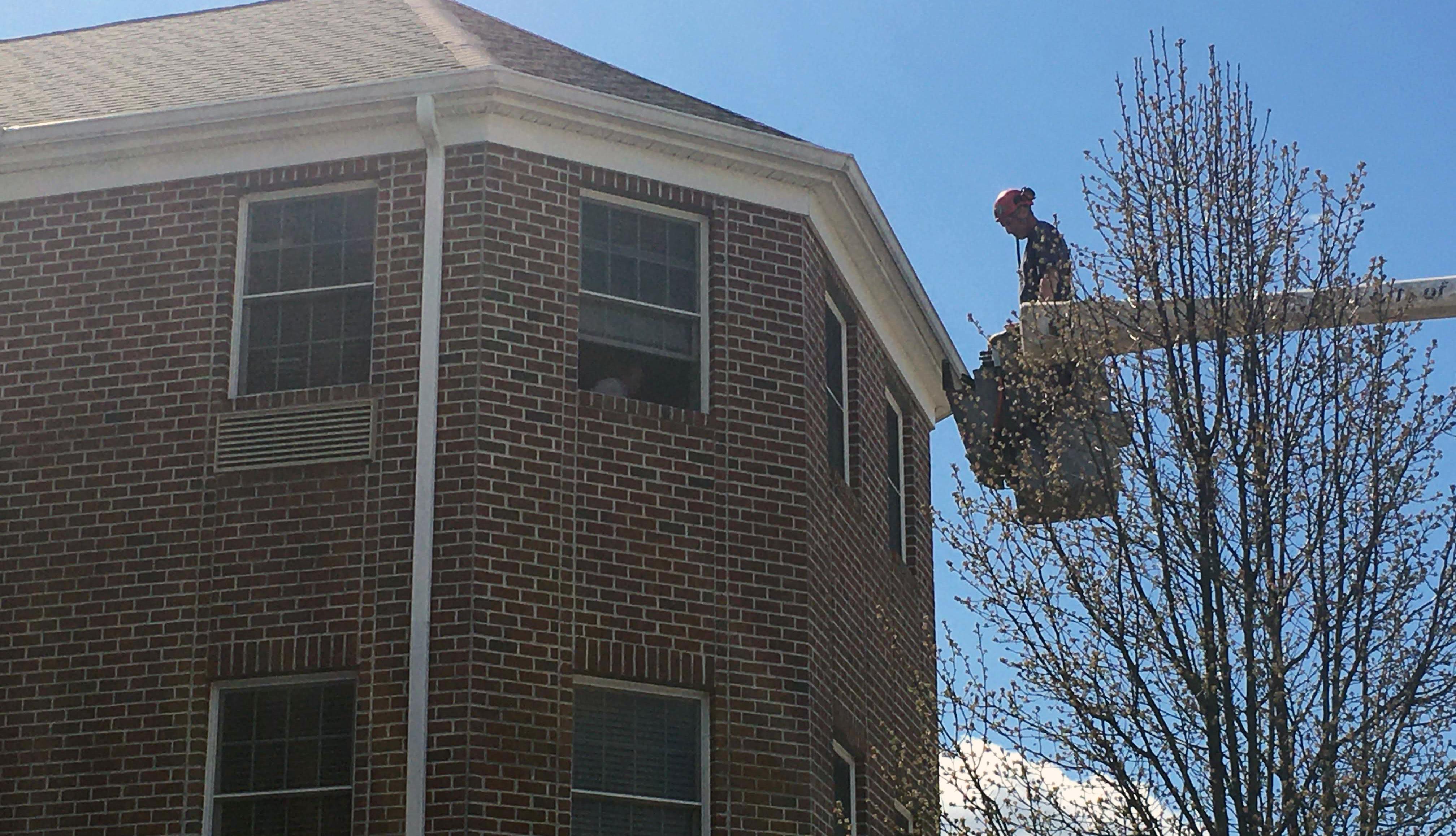 Un hombre subido en una grúa saluda a una persona en un tercer piso
