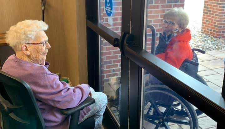 two women interact through the closed glass doors of an assisted living facility r