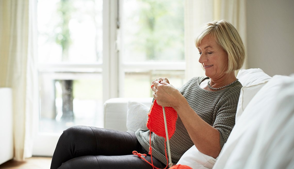 Senior woman knitting while sitting on sofa in house
