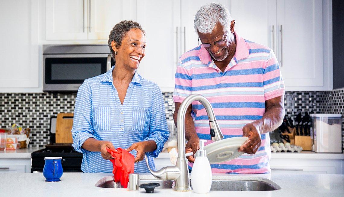 Pareja en la cocina lava los platos mientras y sonríe